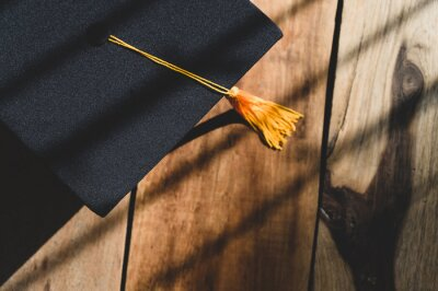 Naklejka Black Graduation Hat placed on Old wood background