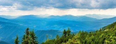 Naklejka Błękitne góry pokryte zielonym lesie. Widok na panoramę szczytów grani