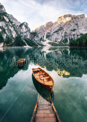 Naklejka Boats and slip construction in Braies lake with crystal water in background of Seekofel mountain in Dolomites in morning, Italy Pragser Wildsee