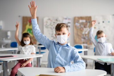 Boy with face mask back at school after covid-19 quarantine and lockdown.