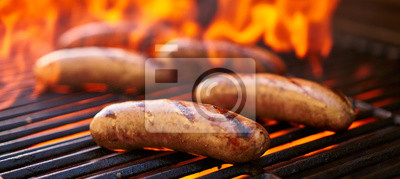 Naklejka brats cooking over flaming barbecue grill