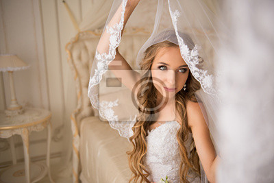 bride in her bright bedroom sitting on a luxurious white bed