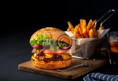 Naklejka Burger smaczne wołowiny z grilla z sałatą, serem i cebulą, serwowane na deski do krojenia na czarny drewniany stół, z lato.