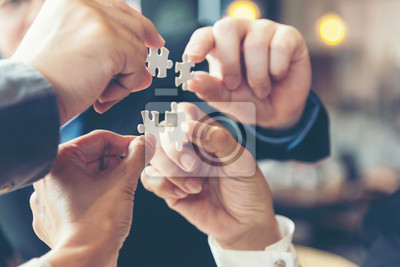 Naklejka Businessman team work holding two jigsaw connecting couple puzzle piece for matching to goals target, success and start up new project in office, select focus. Business Concept.