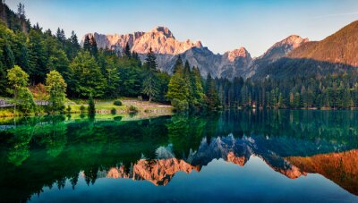 Naklejka Calm morning view of Fusine lake. Colorful summer sunrise in Julian Alps with Mangart peak on background, Province of Udine, Italy, Europe. Beauty of nature concept background.