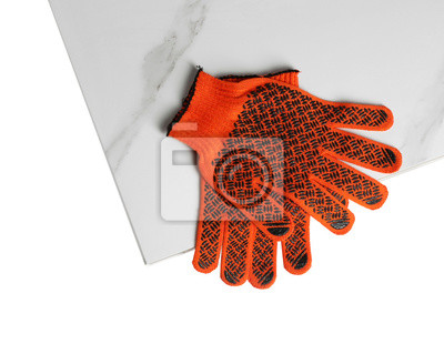 Ceramic tiles and gloves on white background, top view