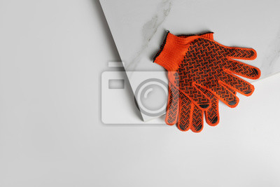 Ceramic tiles and gloves on white background, top view. Space for text