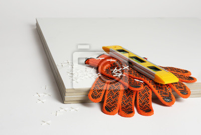 Ceramic tiles with gloves and level on white background