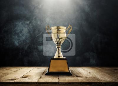 Naklejka Champion złote trofeum umieszczone na drewnianym stole z ciemnym tle kopia przestrzeń gotowy projekt.