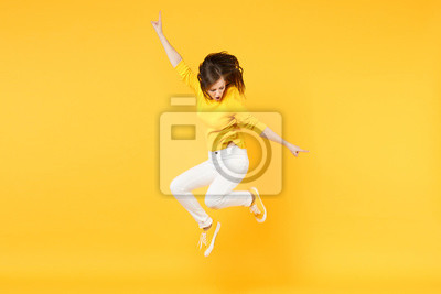 Naklejka Cheerful funny young woman in summer casual clothes jumping and spreading hands isolated on yellow orange wall background in studio. People sincere emotions, lifestyle concept. Mock up copy space.