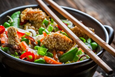 Naklejka Chicken with sesame with vegetables and noodles