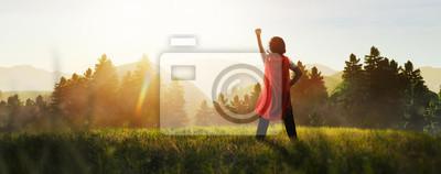 Naklejka child dreaming of super hero in the mountain