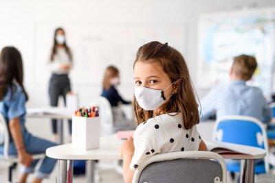 Child with face mask back at school after covid-19 quarantine and lockdown.