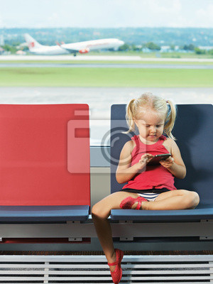 Child with telephone in her hands in the airport