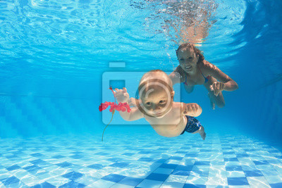 Child with woman diving for a red flower in pool