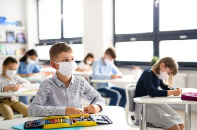 Naklejka Children with face mask back at school after covid-19 quarantine and lockdown.