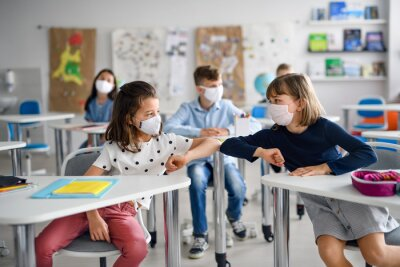 Children with face mask back at school after covid-19 quarantine and lockdown, greeting.