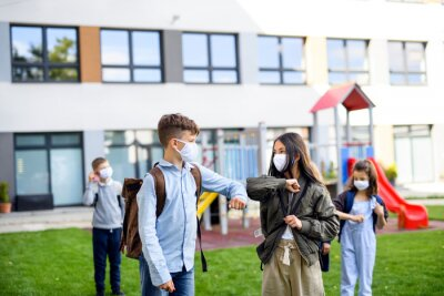 Children with face mask going back to school after covid-19 lockdown, greeting.