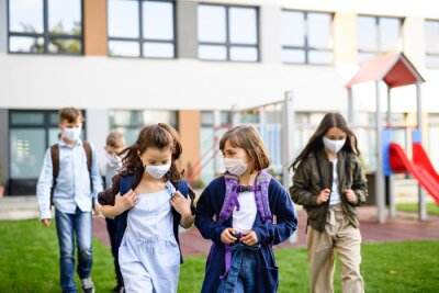 Children with face mask going back to school after covid-19 lockdown, walking outdoors.