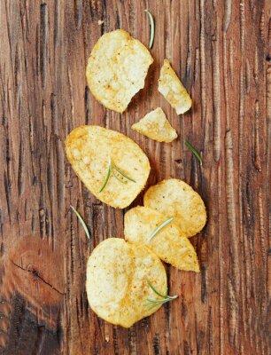 Naklejka Chipsy z solą i rozmarynem na powierzchni drewnianych