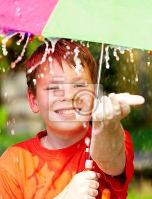 Chłopiec pod parasolem w czasie deszczu ...