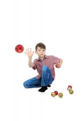 Chłopiec rzuca piłkę choinki. Pojedynczo na białym tle.