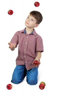 Chłopiec żonglerki z choinki kulkami. Pojedynczo na białym tle. orientacji pionowej.