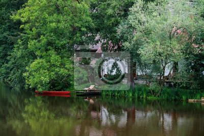 ciche miejsce na wodzie z czerwonym łodzi, domku i drzew