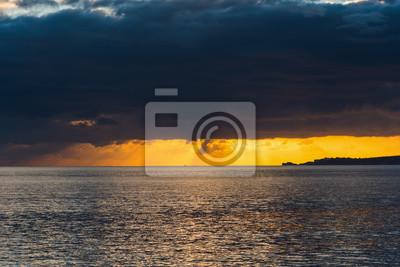 Ciemne chmury nad linią brzegową Alghero o zachodzie słońca
