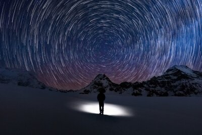 Naklejka Circular Star trails facing north with Polaris the north star in centre and a silhouette human watching the stars move