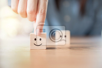 Naklejka Close up customer hand choose smiley face and blurred sad face icon on wood cube, Service rating, satisfaction concept.