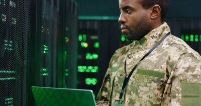 Naklejka Close up of African American male army technician in camouglage costume and hat typing on keyboard of laptop computer while working with secret data at server room. Government analytic center.