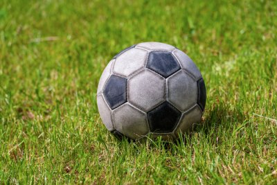 Close-up of an old leather soccer ball on green grass, football sport concept