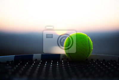 Naklejka Close-up of tennis ball on net of racket at sunset.