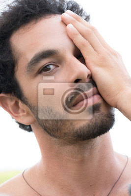 Close up portrait of healthy man with black hair, strong features, looking into the camera with hand covering one half of face
