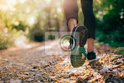 Naklejka Closeup of running shoe of the person running in the nature with beautiful sunlight.