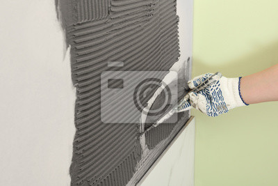 Closeup of worker spreading concrete on wall with spatula, space for text. Tile installation