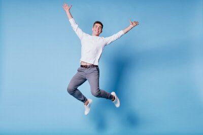 Naklejka Colorful studio portrait of happy young man jumping against blue background.
