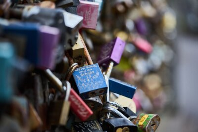 colourful padlocks hanging on fence wire at bridge