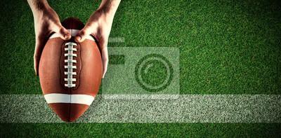 Naklejka Composite obraz Amerykański piłkarz trzyma piłkę nożną
