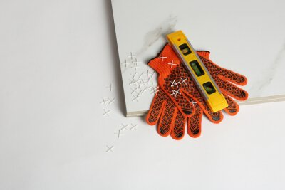 Composition with ceramic tiles and gloves on white background, top view