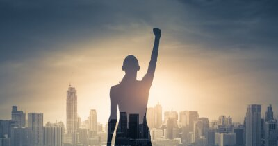 Naklejka confident young woman with fist in the air facing the city. People power and strong young woman concept