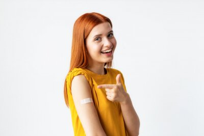 Naklejka Covid-19 vaccinated caucasian happy smiling young woman showing arm with plaster, gray background