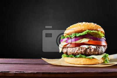 Naklejka Craft burger wołowy na drewnianym stole izolowanych na czarnym tle.