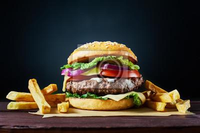 Naklejka Craft wołowiny hamburger i frytki na drewnianym stole odizolowane na ciemnym tle.
