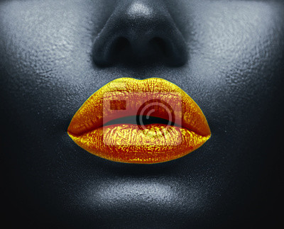 Creative colorful makeup. Bodyart, lipgloss on sexy lips, girl's mouth. Golden lips on black skin