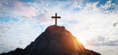 Naklejka Cross on mountain peak at sunset christian religion