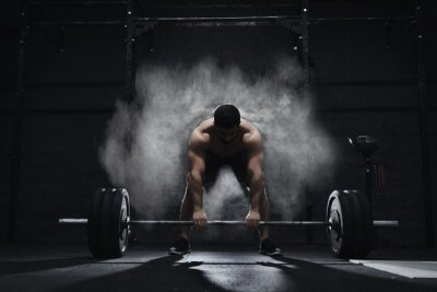 Naklejka Crossfit athlete preparing to lift heavy barbell in a cloud of dust at the gym. Barbell magnesia protection.