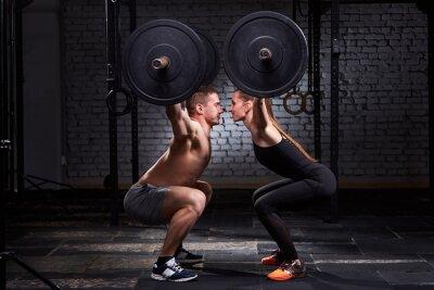 Naklejka Crossfit podnoszenia bar przez kobiety i mężczyzny w grupie treningu przeciwko ścianę z cegły.