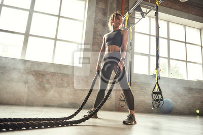 Naklejka CrossFit training. Young athletic woman with perfect body doing crossfit exercises with a rope in the gym.